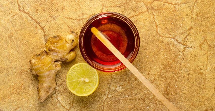 Ingwer, Zitrone und Glas mit Honig auf Tisch