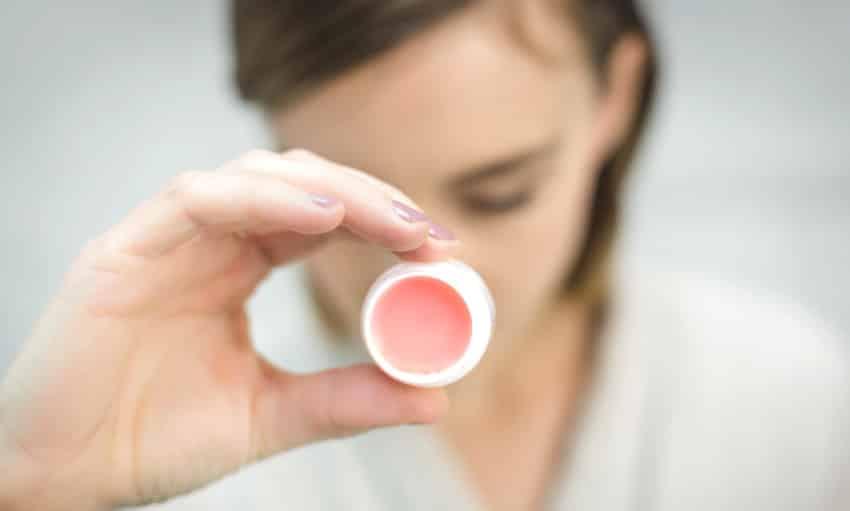 Frau hält geöffneten Kosmetiktiegel in der Hand