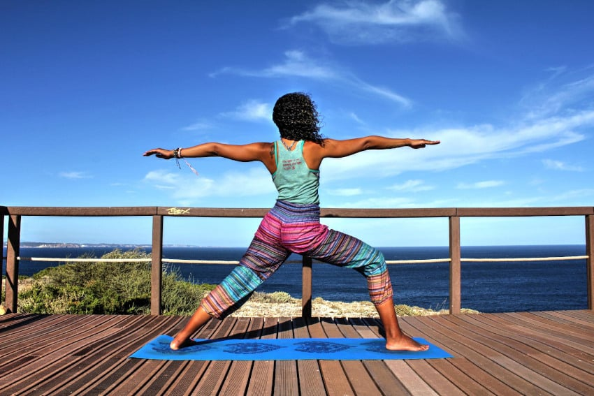 Frau praktiziert Yoga am Meer