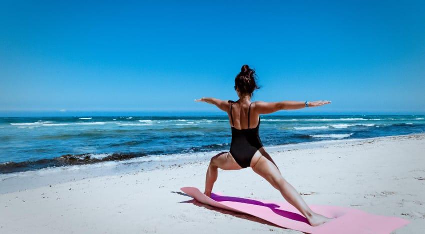 Frau auf Yogamatte am Strand