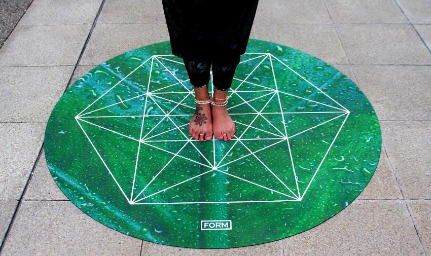 Person steht auf grüner, runder Yogamatte