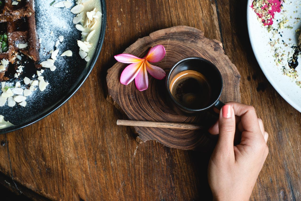 Kaffeetasse auf Baumscheibe mit Blume