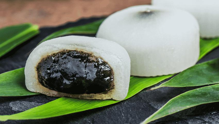 Mochis mit schwarzer Füllung (Bohnenpaste) auf grünen Blättern