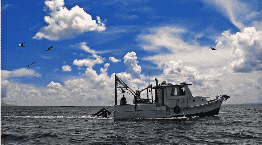 Fischerboot, blauer Himmel mit Sonnenschein