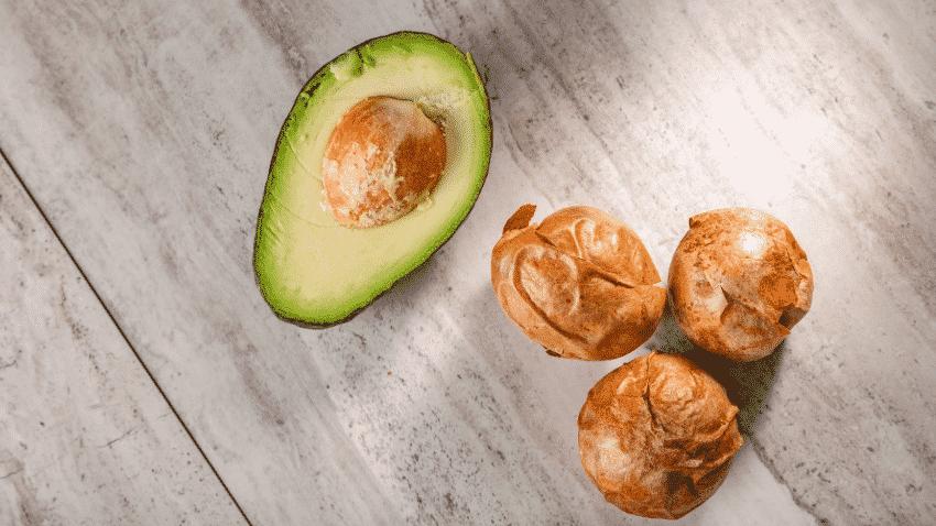 halbe Avocado mit drei Avocadokernen daneben