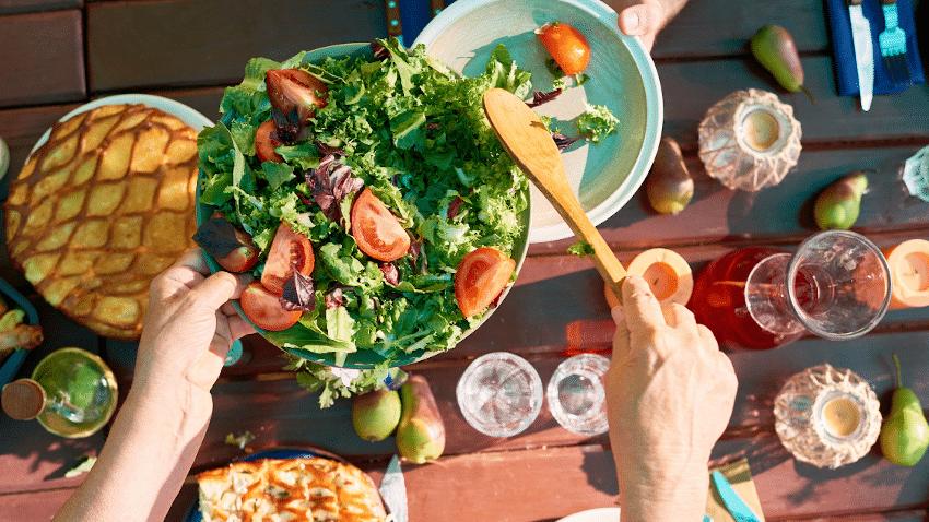 Gedeckter Tisch von oben mit Salat, Brot und Getränken