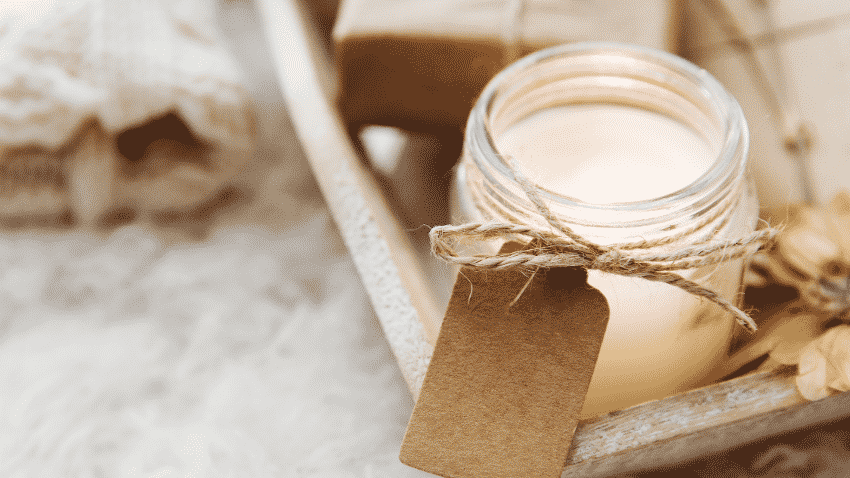 weiße Kerze in Glas auf Holztablett