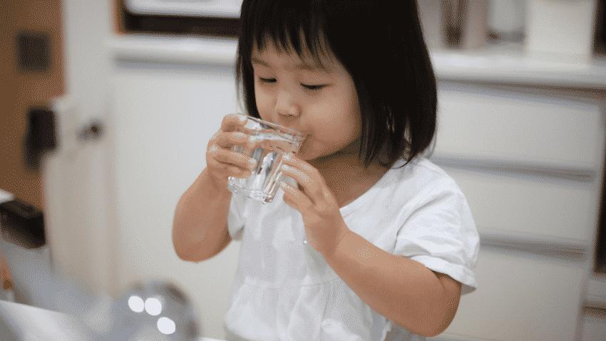 Mädchen trinkt Leitungswasser aus einem Glas in der Küche
