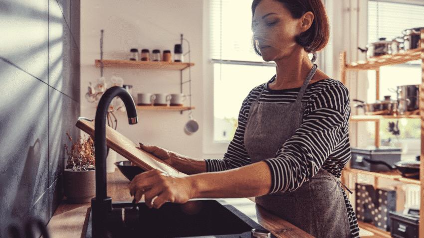 Frau spült Küchenbrett aus Holz