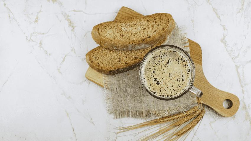 zwei Scheiben Brot und Getränk auf Holzbrett von oben