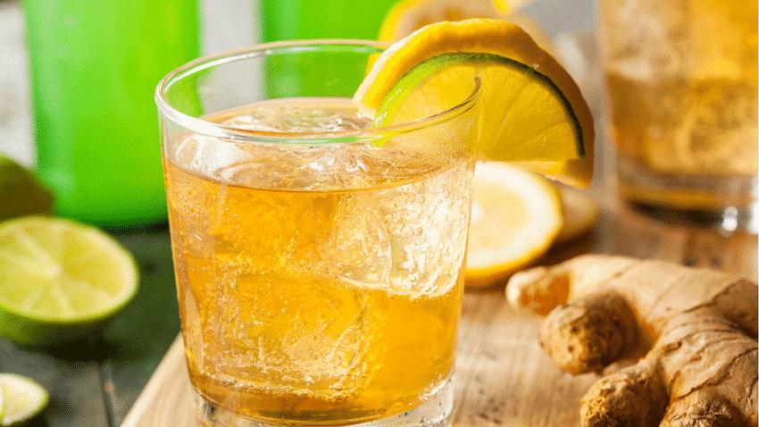 Ingwerbier in einem Glas mit Zitronenscheiben und frischer Ingwerwurzel