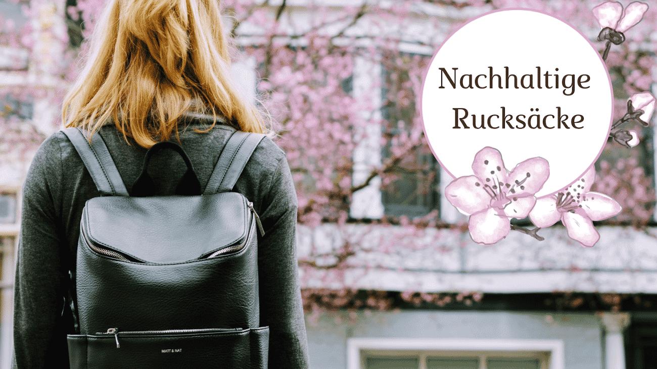 Frau von hinten mit schwarzem Rucksack, Baum mit rosa Blüten verschwommen im Hintergrund