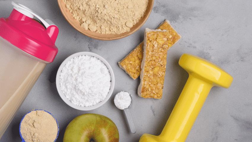 Proteinpulver, Banane, Shaker, Hantel, Apfel und Riegel von oben