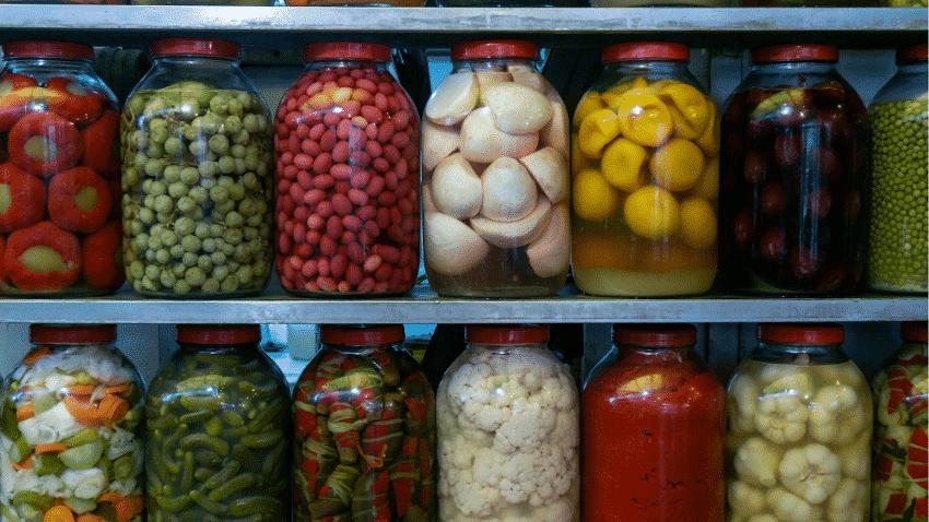 mehrere Gläser mit fermentiertem Gemüse in einem Metallregal
