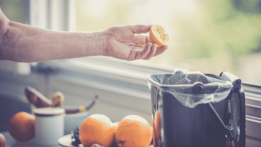 Hand mit Zitronenschale vor Bokashi in Küche