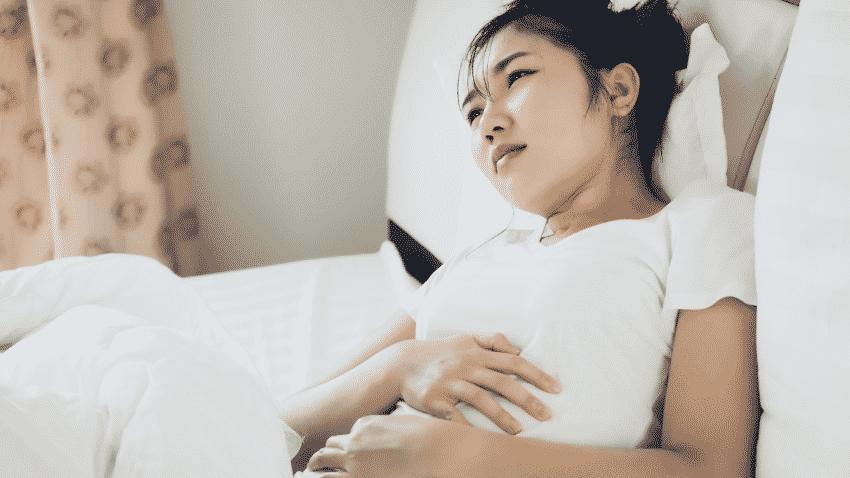 Junge asiatische Frau im Bett mit schmerzverzehrtem Gesicht
