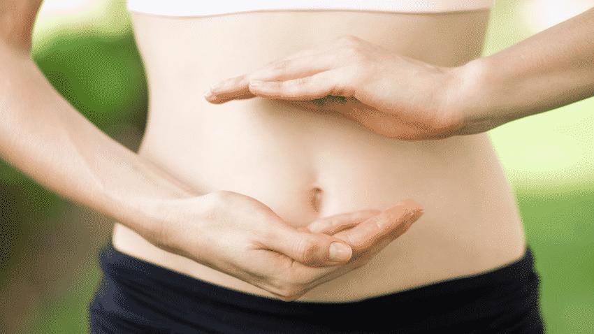 Frau hält sich die Hände vor ihrem nackten Bauch