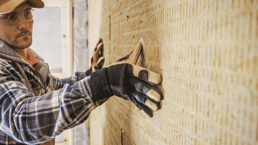 Handwerker setzt zum Dämmen eine Holzfaserplatte ein