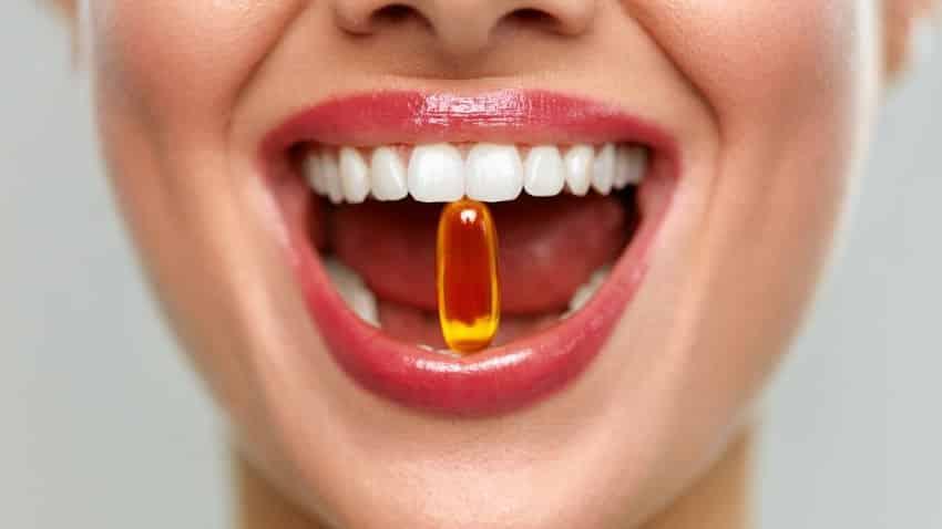 großer Frauenmund mit Kapsel zwischen den Zähnen