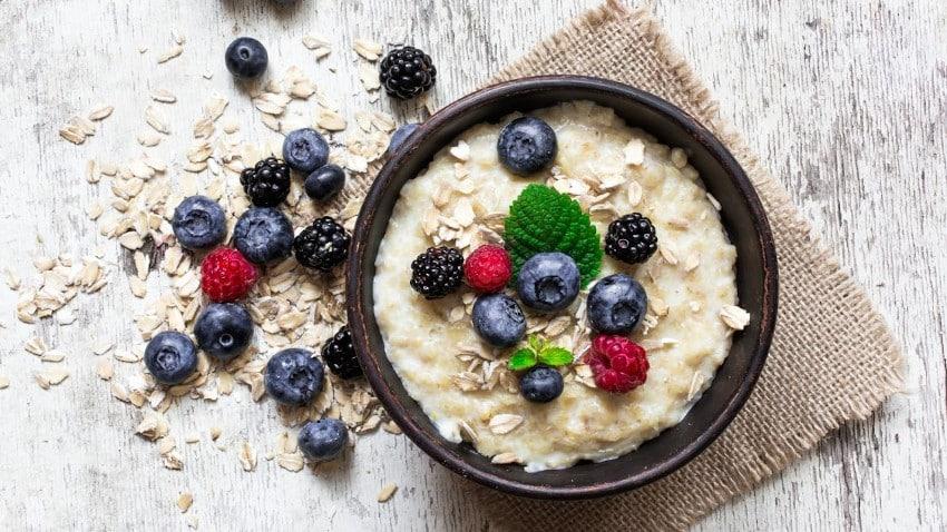 Porridge mit Früchten in dunkler Schüssel von oben