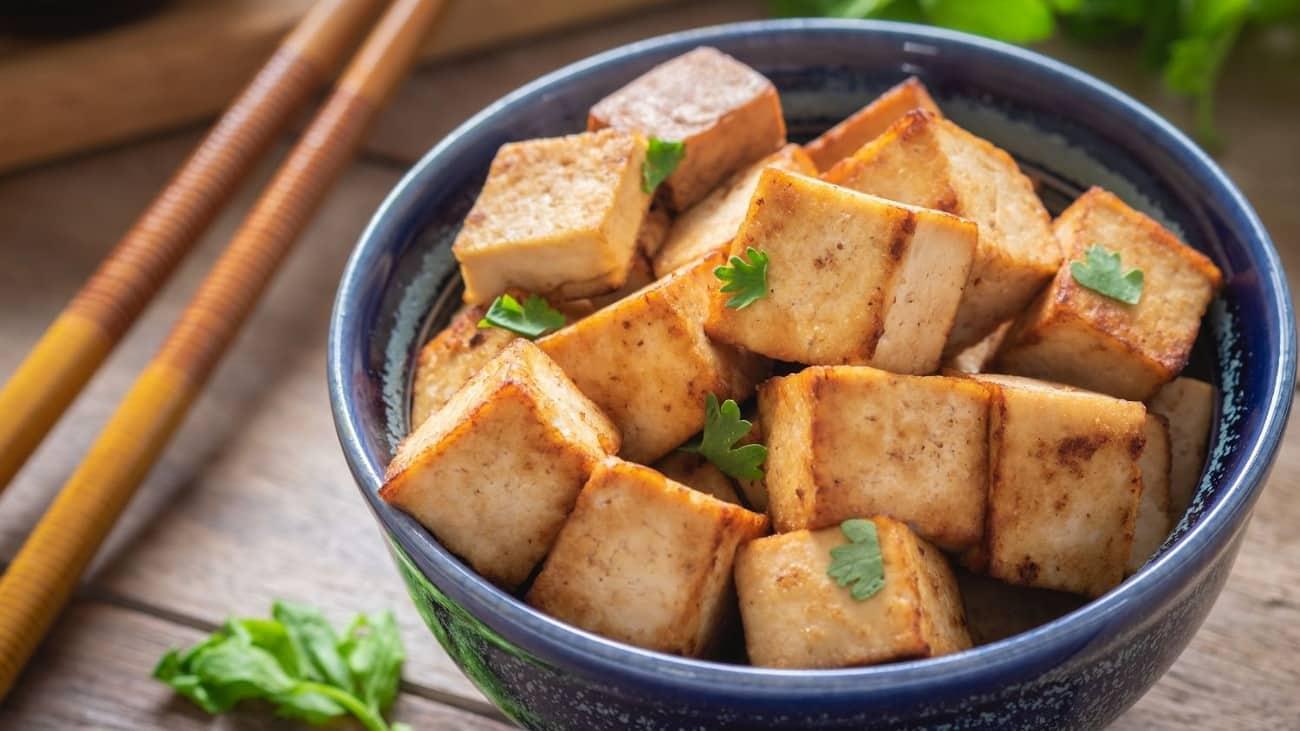 gebratene Tofuwürfel in blauer Schale und Stäbchen daneben