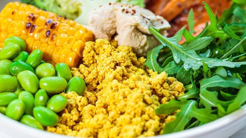 Schüssel mit veganem Rührei, Sojabohnen, Rucola, Maiskolben, Hühnchen und Süßkartoffeln